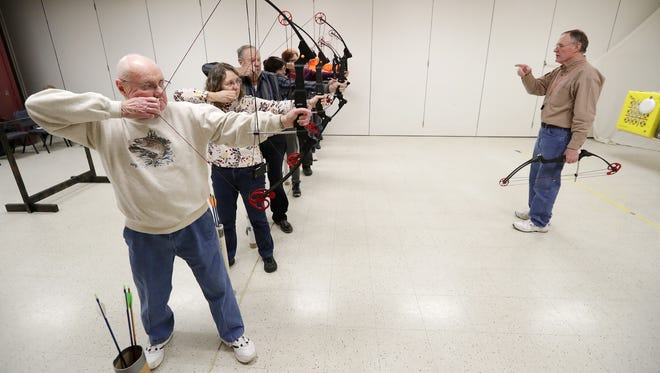 Doug Thompson, right, leads an archery class for senior citizens at the Brown County UW-Extension on Tuesday, The county is moving programs and offices out of the building after agreeing to sell it to the Green Bay Area School District.