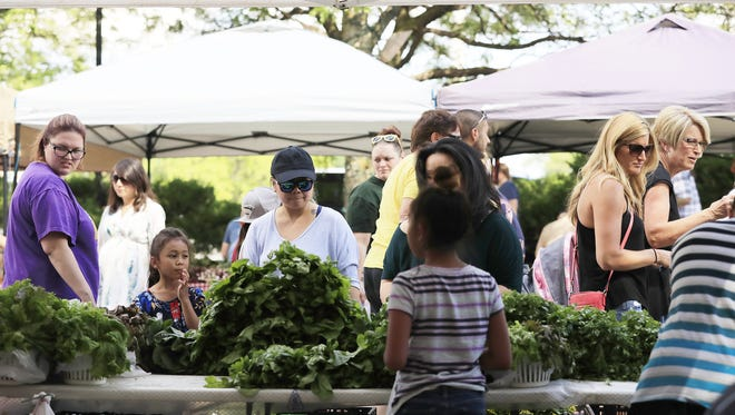 Customers browse a vegetable stand Wednesday at the Farmers' Market On Broadway in Green Bay.