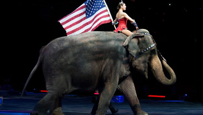 "This file photo taken on March 19, 2015 shows a performer riding an elephant holding a US national flag during a Ringling Bros. and Barnum & Bailey Circus performance in Washington, DC. Ringling Bros. and Barnum & Bailey Circus announced Saturday, January 14, 2016 it will host its final show in May, ending ""The Greatest Show on Earth"" after 146 years. Company executives cited high operating costs and declining ticket sales after the American circus retired its elephants -- a main draw -- as some of the factors that triggered its downfall."