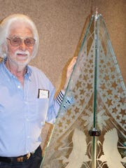 Stan Saran stands with his tree of etched glass.