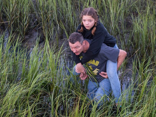 A man carries his daughter through the mud just before