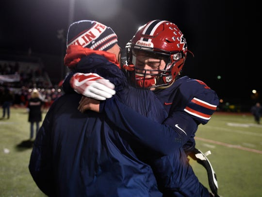 Franklin quarterback Jacob Kelbert hugs his father Chris, the head coach, after a thrilling 31-29 Region 2 final win over Flushing.