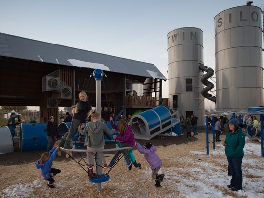 Children swarm the playground at the new Twin Silo Park in south Fort Collins on Thursday, November 9, 2017. The park made its formal debut with a ribbon-cutting ceremony and tours of the area.