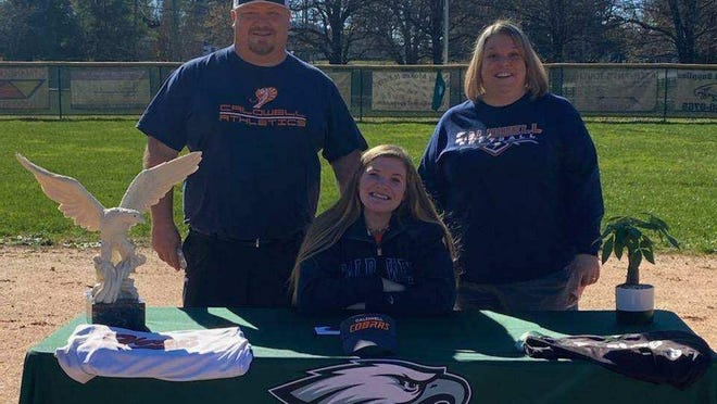 With her parents, Wayne and Corey, as witnesses, East Henderson High softball standout Adorey Jones signs with Caldwell Community College earlier this month at East.