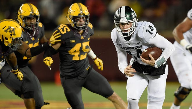 Brian Lewerke #14 of the Michigan State Spartans carries the ball against the Minnesota Golden Gophers during the third quarter of the game on October 14, 2017 at TCF Bank Stadium in Minneapolis, Minnesota. The Spartans defeated the Gophers 30-27.