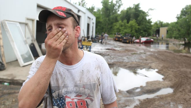 Mike Mikeklarenbeek, owner of Rapid Auto Repair, which was affected by flood waters of the Rock River, reacts as he talks about the flooding of his business seen here on Wednesday, June 18, 2014, in Rock Rapids, Iowa.