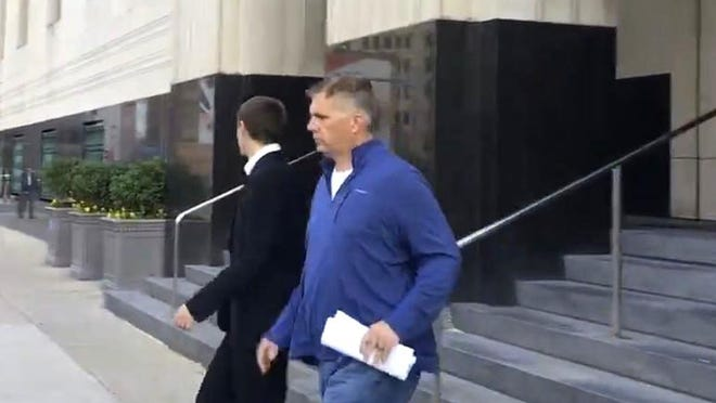 Macomb Twp. Trustee Clifford Freitas exits federal court in Detroit after being charged in a bribery case.