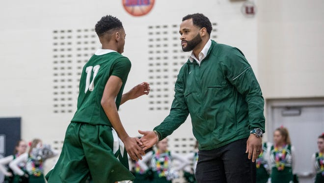 New Haven coach Tedaro France II claps hands with Tavares Oliver Jr. during a regional final basketball game Wednesday, March 15, 2017 at North Branch High School. New Haven defeated Pontiac Notre Dame Prep 71-44.