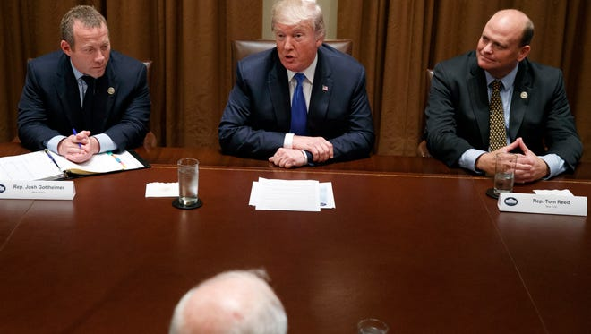 Rep. Josh Gottheimer, D-N.J., left, and Rep. Tom Reed, R-N.Y., right, listen as President Donald Trump speaks during a meeting with a bipartisan group of lawmakers in the Cabinet Room of the White House, Wednesday.
