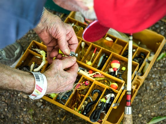 World War II veteran Norbert Jost, 92, tries to decide on a lure while sorting through his tackle box Saturday, June 30, on Lake Sagatagan in Collegeville.