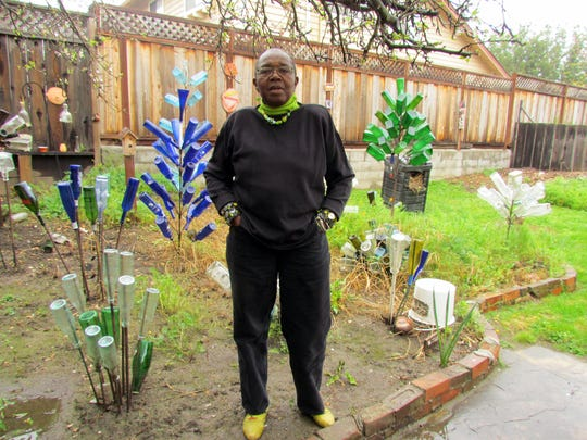 Rachel Clark, a professional quilter and sewing instructor from Watsonville, stands in her garden near her bottle trees.