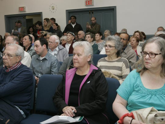 a large crowd listens to presentations at a public