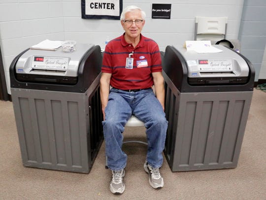 Poll worker Dick Johnsen sits between two voting machines