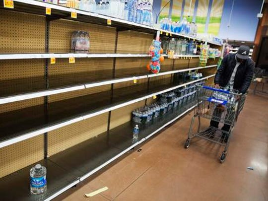 Shelves of bottles of water sit mostly empty at a supermarket in Atlanta, Friday, Jan. 6, 2017. Shoppers emptied shelves of bread and milk, road workers began working 12-hour shifts, and states of emergency were declared in Alabama, Georgia and the Carolinas ahead of a winter storm stalking the South.
