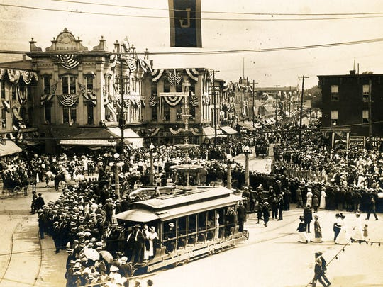 "The H. M. White Building as it looked in 1914 during the ""Old Home Week"" Firemen's Parade"