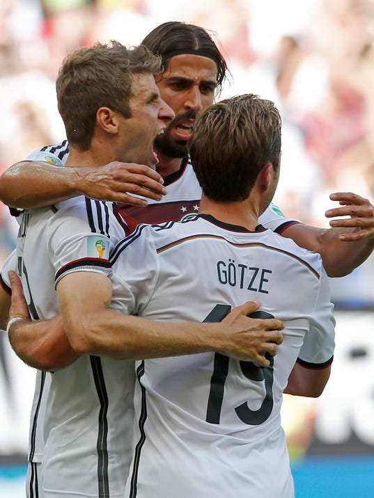 Germany's Thomas Mueller, left,  celebrates with Mario Goetze after scoring the opening goal during the group G World Cup soccer match between Germany and Portugal at the Arena Fonte Nova in Salvador, Brazil, Monday, June 16, 2014.   (AP Photo/Matthias Schrader)