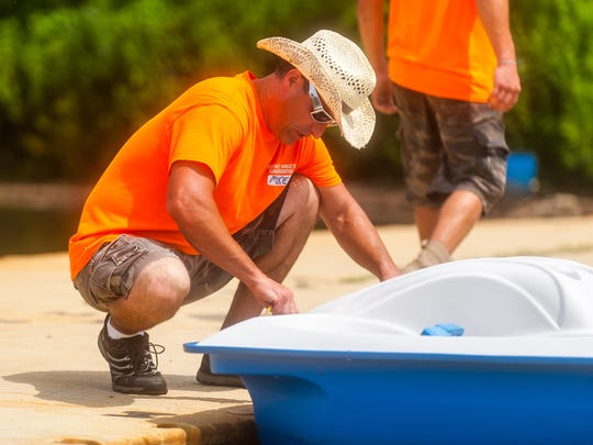Mike Martin ties up a paddle boat for Cowboy Mike's Canoe Rental at Cooper River Park on Saturday, July 15.