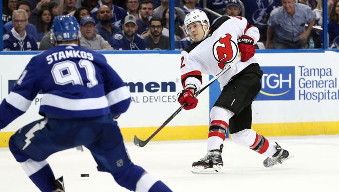 New Jersey Devils defenseman Ben Lovejoy (12) photos as Tampa Bay Lightning center Steven Stamkos (91) defends during the second period of game one of the first round of the 2018 Stanley Cup Playoffs at Amalie Arena.