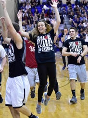 Abby Bellows leaps with other seniors during Color