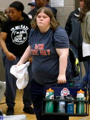 Oakland girls basketball manager Elizabeth Schott gathers water bottles during Tuesday's game at Siegel.