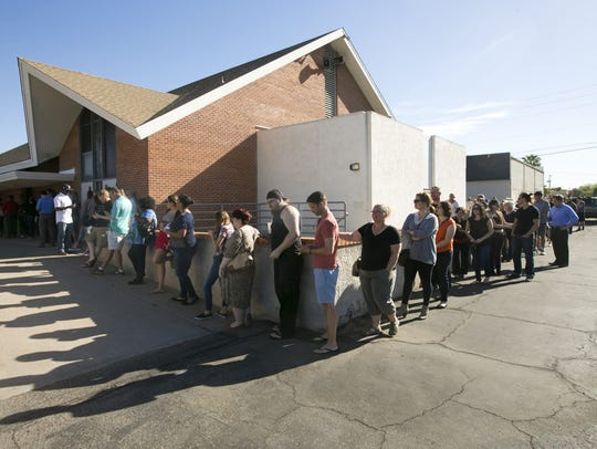 People wait in line to vote at the polling place at