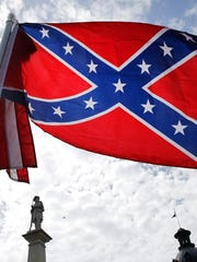 A protester waves a Confederate battle flag in front of the South Carolina statehouse in Columbia Thursday, July 9, 2015.