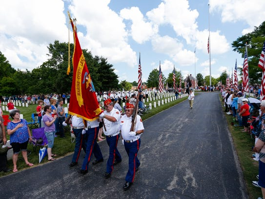 A color guard from the Marine Corps League marches