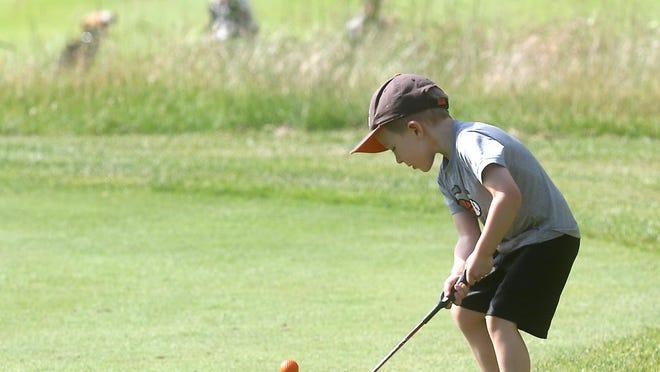 Owen Claxon, 4, hits the ball while at Oak Shadows Golf Club with his dad.