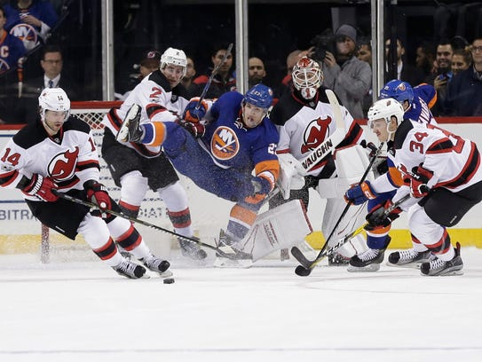 Islanders' Anders Lee, center, Devils goalie Keith