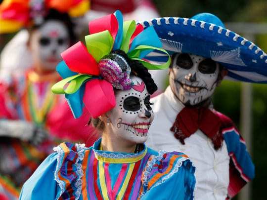 Performers participate in the Day of the Dead parade