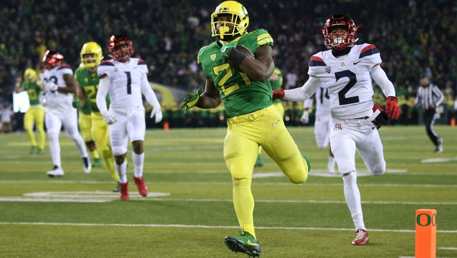 Oregon running back Royce Freeman, center, breaks through the Arizona defense, including Arizona's Lorenzo Burns, right, for a touchdown during the second quarter on Saturday, Nov. 18, 2017, in Eugene, Ore.