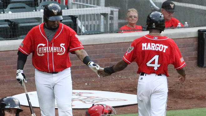 Manuel Margot, 4, gets a hand from Hector Sanchez after scoring a run early in the game against the Memphis Redbirds in a past game.