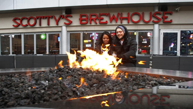 Hosanna Webb and Aaron Hubbard, both of Indianapolis, brave the elements as they have a drink and warm themselves by the fire pit in front of Scotty's Brewhouse, 1 Virginia Ave., Indianapolis, Monday, Nov. 21, 2011.