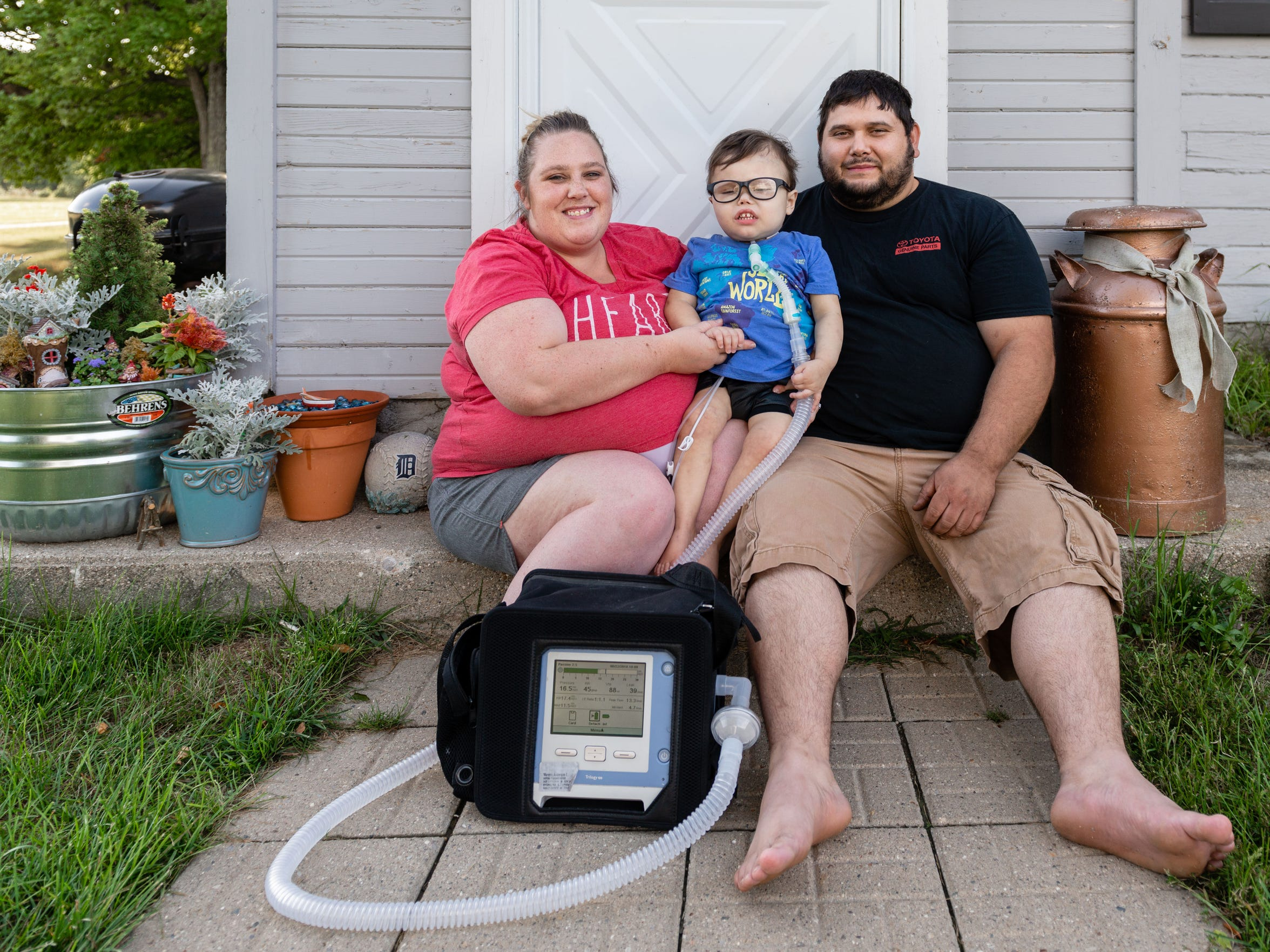 Anderson Moreno uses a portable ventilator because of his impaired lung capacity. He is shown with his parents, Alicia and Andy Moreno.