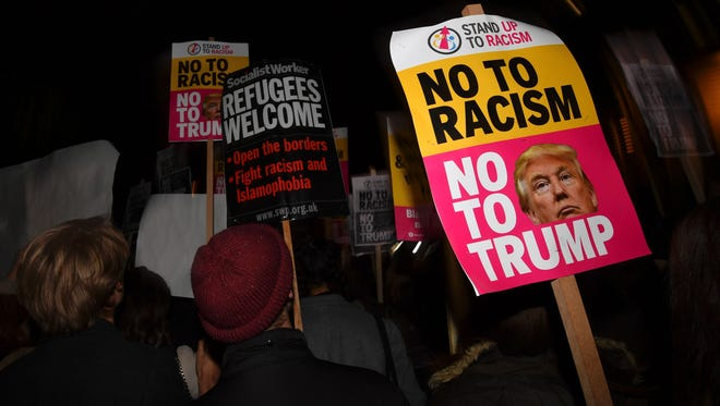 "Demonstrators hold placards that read ""No to racism, no to Trump"" during a protest outside the US Embassy in London on November 9, 2016 against US President-elect Donald Trump after he was declared the winner of the US presidential election.  Political novice and former reality TV star Donald Trump has defeated Hillary Clinton to take the US presidency, stunning America and the world in an explosive upset fueled by a wave of grassroots anger. / AFP / BEN STANSALL        (Photo credit should read BEN STANSALL/AFP/Getty Images)"