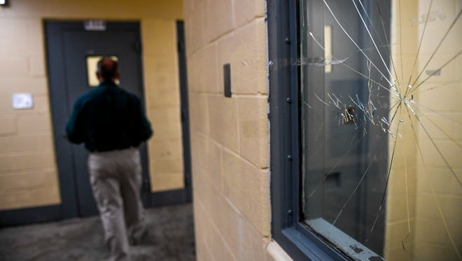 A cracked panel of glass can be seen in the window of a holding cell for mental health patients at Madison County Jail in Jackson, Tenn., on Wednesday, Aug. 29, 2018.