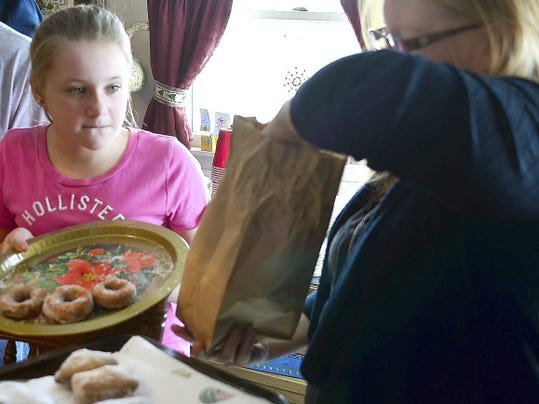 Makensie Husson, left, of Dover helps her aunt Stephanie Diehl of East Berlin powder the fasnachts during a family gathering in Winterstown Saturday, Feb. 7, 2015. Family members met at Tim and Cathy Staab's house to make fasnachts. Stop in as the family gathers in a video at yorkdispatch.com. Randy Flaum photo - rflaum@yorkdispatch.com