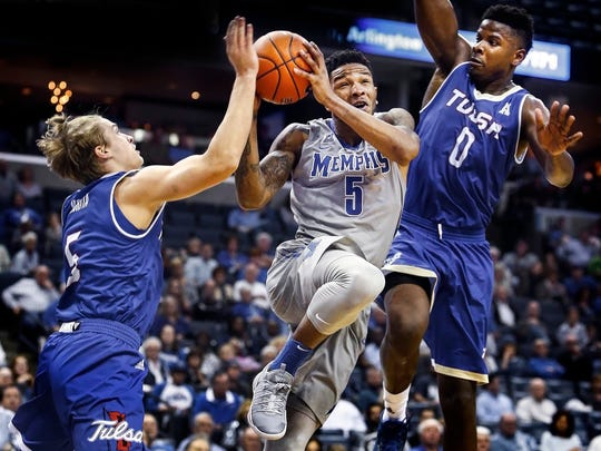 University of Memphis guard Markel Crawford (middle) drives for a reverse layup against University of Tulsa defenders Lawson Korita (left) and Junior Etou (right) during second half action of a Tigers 66-44 victory at the FedExForum. Crawford finished with a game-high 19 points on 8-13 shooting.