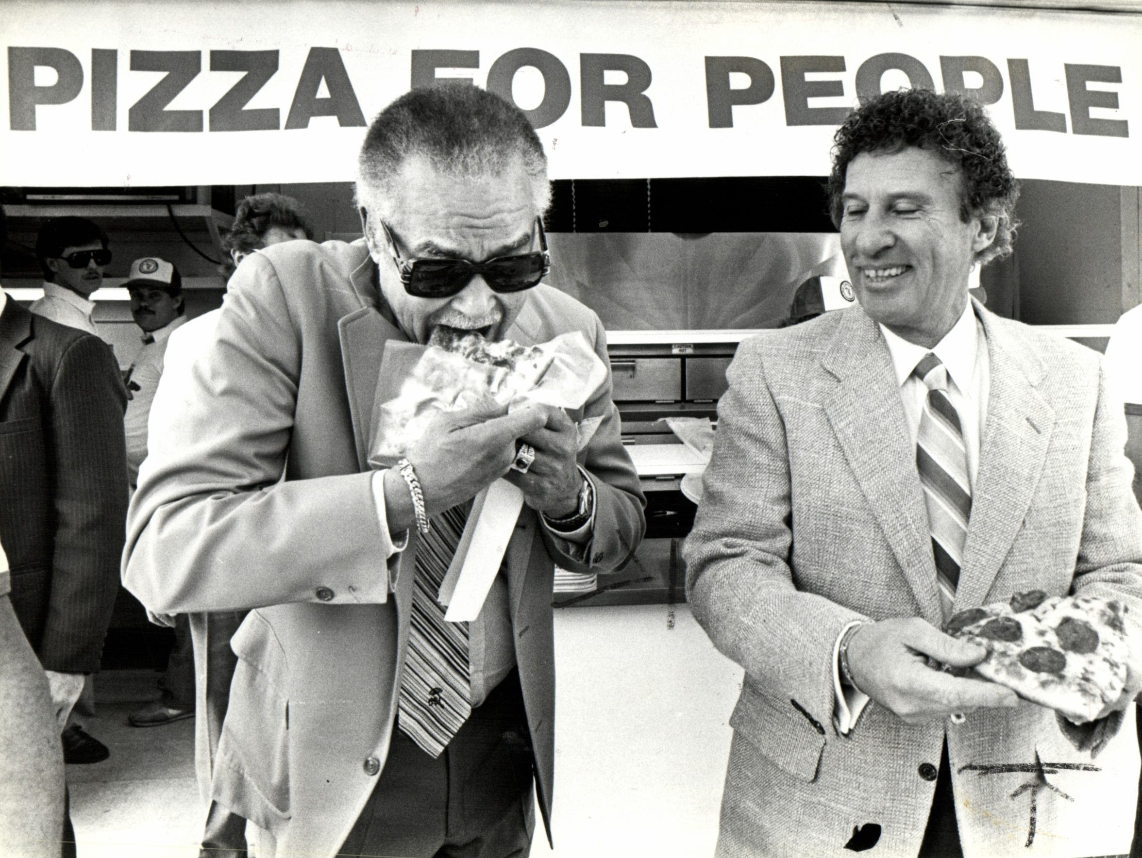 Detroit Mayor Coleman Young eats a slice of pizza with