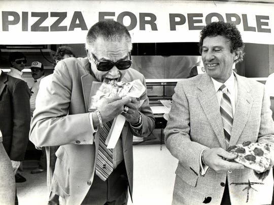Detroit Mayor Coleman Young eats a slice of pizza with Little Caesars Pizza owner Mike Illitch during a fundraiser for the hungry in Detroit in 1985.