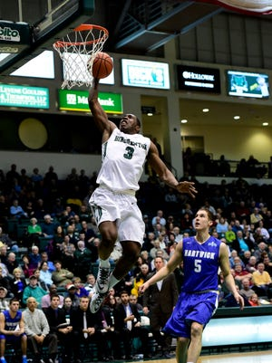Former Binghamton University star Jordan Reed goes up for a dunk in front of Hartwick's Trevor Norton during a game in the Events Center on Nov. 19, 2014.