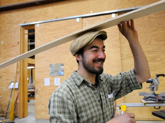 Great Lakes Boat Building School student Benjamin Davant of Belfort, France carries freshly-cut wood for  the sides of a Cornish Pilot Gig boat being built for the U.S. Navy's USS Constitution at the school in Cedarville, Michigan off the Les Cheneaux Islands 5/13/2015.  Students at the school learn a wide variety of construction skills and techniques to hand build fine boats.