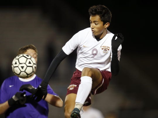 Florida High'€™s Johnny Garcia leaps to kick the ball past a Marianna defender during their District Semifinal game at Rickards High School on Wednesday.