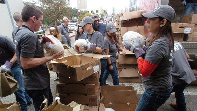 Thomas J. Henry staff members take frozen turkeys from boxes out of a semi-truck and place them in bags to give to people.