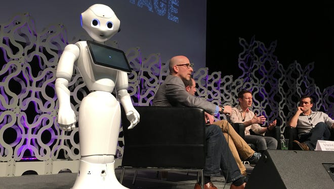 Pepper the robot looks on as panelists discuss advances in robot technology at the SXSW Interactive Festival in Austin. Robots played a key role at this year's tech gathering.
