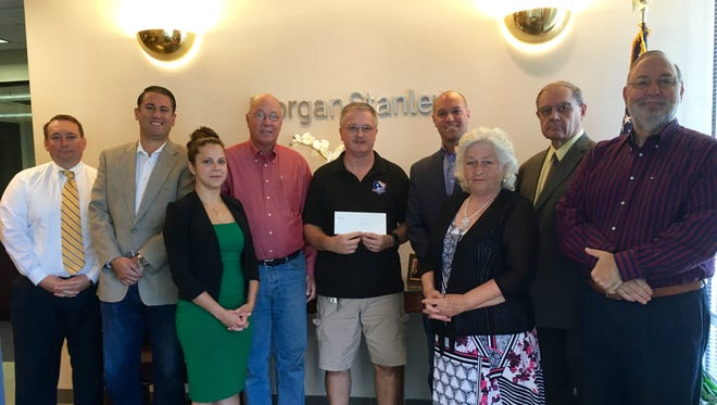 """Morgan Stanley Wealth Management's Vineland branch presented a check for $155 to First Presbyterian Church of Vineland's food pantry on Aug. 5. The check represented proceeds of the branch's """"Casual Charity Fridays"""" program. (From left) financial advisers Charles Allen and John Fitzgerald; sales assistant Jenna Biagi; financial adviser Jack Whiteway; Dave McKishen of First Presbyterian Church; branch manager and financial adviser Michael Ahrens; sales assistant Maria Grant; and financial advisers Al Lupcho and Rich Catrambone are pictured. Financial advisers Rob McAllister, Wayne Campbell, Steven Caltabiano and Vanessa Brown, and sales assistants Sarah Viruet and Rob McAllister Jr., who also supported the program, are not pictured."""