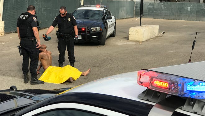 Visalia officer Tim Haener gives a man water after the naked man led officers on a chase.