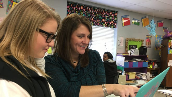 DeSoto Central High School English II teacher Tara Wooley, looks over a paper with sophomore Gracie Pipkin. From her laptop Wooley can assign, review, notate and grade her students' work.