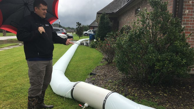 Stafford Barnett of Lafayette explains how the water barrier he built and placed around his home will help keep floodwaters out as Tropical Storm Harvey approaches.