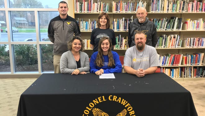 Courtney Britt, surrounded by her parents and coaches, officially commits to Notre Dame College.